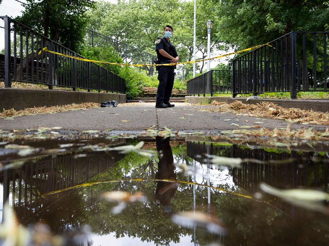 A New York City police officer stands guard on July 7th, 2020 at the scene where a 27-year-old man was found shot to death in a park in Crown Heights. JUSTIN LANE/EPA-EFE/Shutterstock